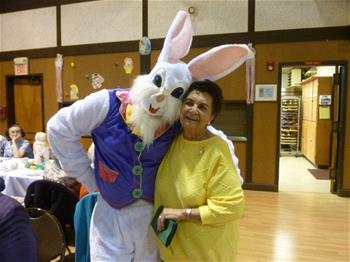 Senior with easter bunny at holiday luncheon